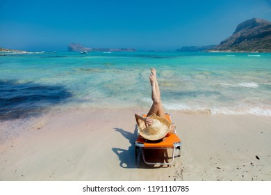 Young redhead girl in black bikini and with hat lying down on lounger on Balos beach, west Crete, Greece. Summertime season vacation, July