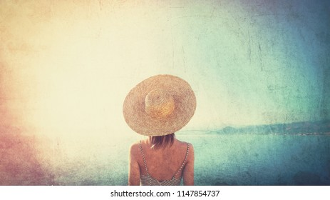 Young redhead girl in hat and dress with sea coastline on Balos, Crete, Greece. Image in retro style