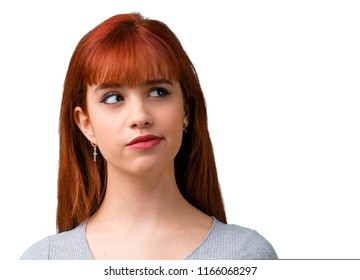 Young redhead girl having doubts and with confuse face expression