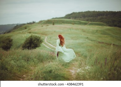 Young redhead girl in medieval dress walking through field with sage flowers. Freedom concept. Fantasy. Wind