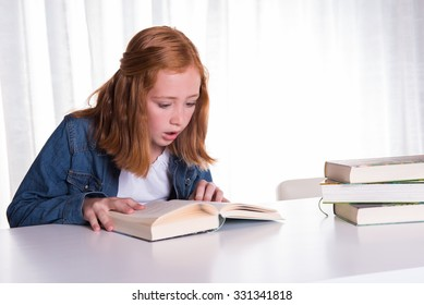 young redhead girl reading in books - she is scared