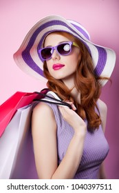 Young redhead girl with shopping bags and purple clothes on pink background