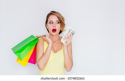 Young redhead girl with shopping bags and money on white background