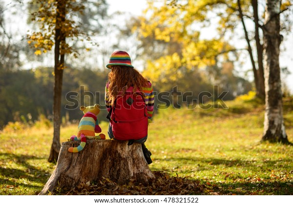 Young redhead girl sitting on stump with her alive toy cat and dreaming