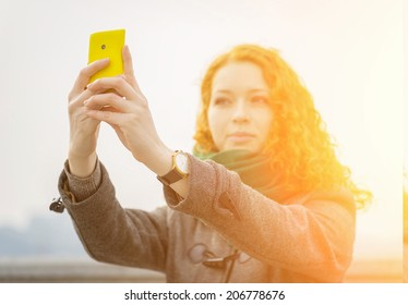 Young redhead girl taking a selfie outdoors on sunny day. With sunshine effect.
