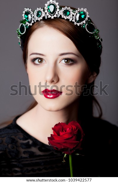 Young redhead girl with tiara and rose on grey background