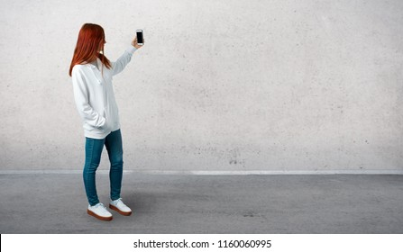 Young redhead girl in an urban white sweatshirt with glasses taking a selfie with the mobile and standing on a vintage gray wall