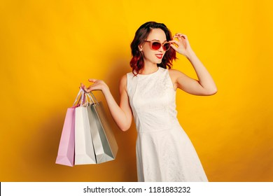 Young redhead girl in white dress with shopping bags on yellow background.