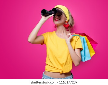 Young redhead girl in yellow t-shirt and blue jeans holding colorful bags and binoculars on pink background