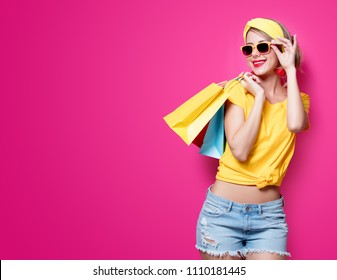 Young redhead girl in yellow t-shirt and blue jeans holding a colorful bags on pink background
