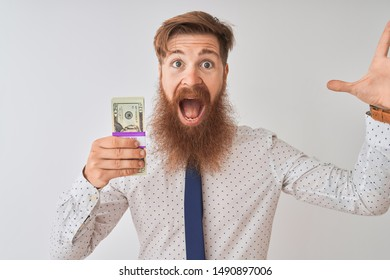Young redhead irish businessman holding dollars standing over isolated white background very happy and excited, winner expression celebrating victory screaming with big smile and raised hands
