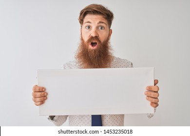 Young redhead irish man holding banner standing over isolated white background scared in shock with a surprise face, afraid and excited with fear expression