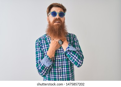 Young redhead irish man wearing casual shirt and sunglasses over isolated white background shouting and suffocate because painful strangle. Health problem. Asphyxiate and suicide concept.
