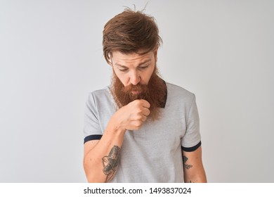 Young redhead irish man wearing grey polo standing over isolated white background feeling unwell and coughing as symptom for cold or bronchitis. Healthcare concept.