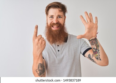 Young redhead irish man wearing grey polo standing over isolated white background showing and pointing up with fingers number six while smiling confident and happy.