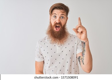 Young redhead irish man wearing polo standing over isolated white background pointing finger up with successful idea. Exited and happy. Number one.