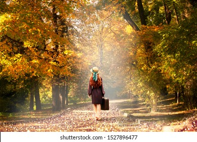 Young redhead lady woman in polka dot dress and hat with suitcase in retro style walking away along a park road with golden yellow autumnal trees. Outdoor autumn garden relaxation, travel to fairytale