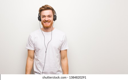 Young redhead man cheerful with a big smile. Listening to music with headphones.