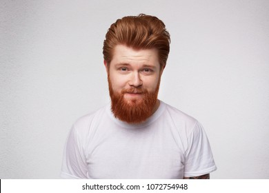Young redhead man with heavy, massive beard smiles and feels happy. Portrait of pleased, joyful male. Isolated over studio white wall