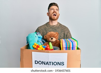 Young redhead man holding donation box with toys angry and mad screaming frustrated and furious, shouting with anger looking up.