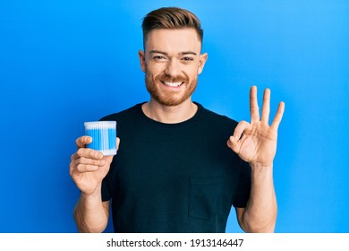 Young redhead man holding earwax cotton remover doing ok sign with fingers, smiling friendly gesturing excellent symbol