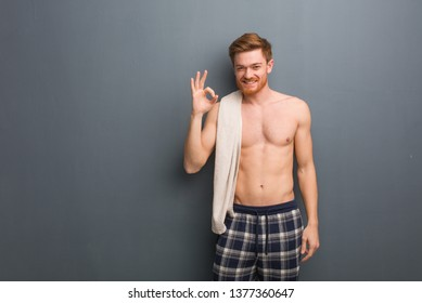 Young redhead man holding a towel cheerful and confident doing ok gesture. He is holding a white towel.