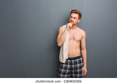 Young redhead man holding a towel doubting and confused. He is holding a white towel.