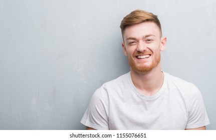 Young redhead man over grey grunge wall with a happy face standing and smiling with a confident smile showing teeth
