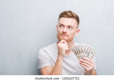 Young redhead man over grey grunge wall holding dollars serious face thinking about question, very confused idea