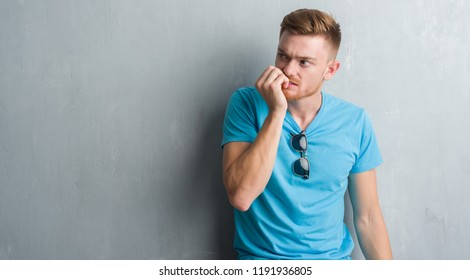 Young redhead man over grey grunge wall wearing casual outfit looking stressed and nervous with hands on mouth biting nails. Anxiety problem.
