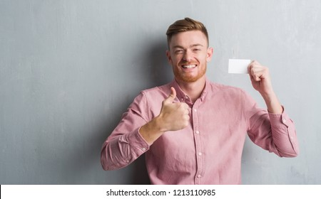 Young redhead man over grey grunge wall holding blank visit card happy with big smile doing ok sign, thumb up with fingers, excellent sign