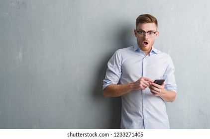 Young redhead man over grey grunge wall sending message using smartphone scared in shock with a surprise face, afraid and excited with fear expression