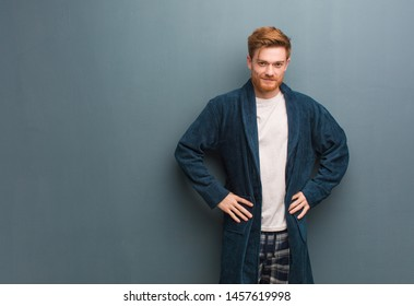 Young redhead man in pajama with hands on hips