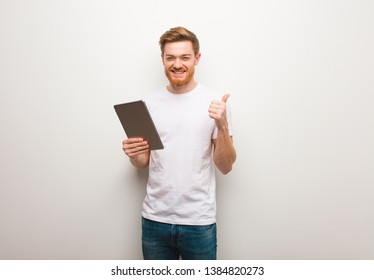 Young redhead man smiling and raising thumb up. Holding a tablet.