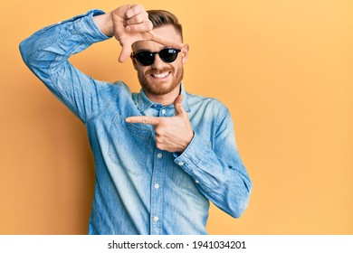 Young redhead man wearing stylish sunglasses smiling making frame with hands and fingers with happy face. creativity and photography concept.