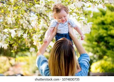 Young redhead mother and child have a leisure in springtime flowering garden in sunny day.