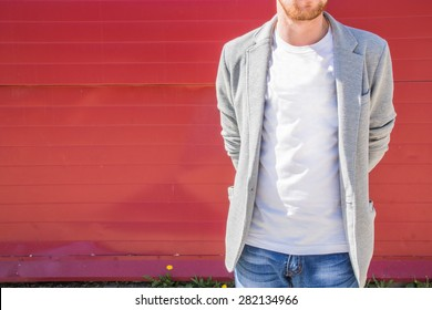 Young redhead muscular sexy man with beard wearing jeans, white T-shirt and grey cotton jacket standing near a red wall with hands behind a his back