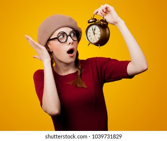 young redhead nerd girl with eyeglasses and alarm clock on yellow background