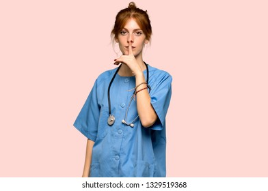 Young redhead nurse showing a sign of silence gesture putting finger in mouth over pink background