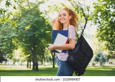 Young redhead outdoors. Female student walking in the park with an exercise book and backpack. Education concept