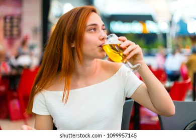 Young redhead pretty girl enjoying a beer at a mall