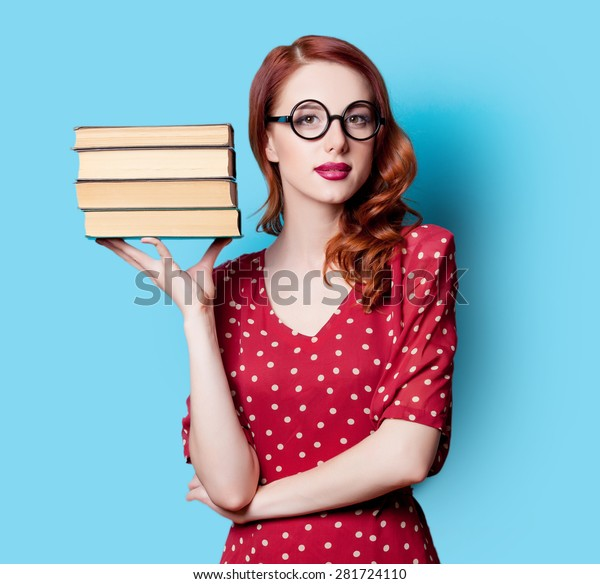 Young redhead teacher in red polka dot dress with books on blue background.