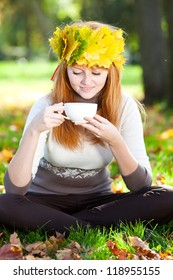 young redhead teenager woman in a wreath of maple leaves with cup of tea