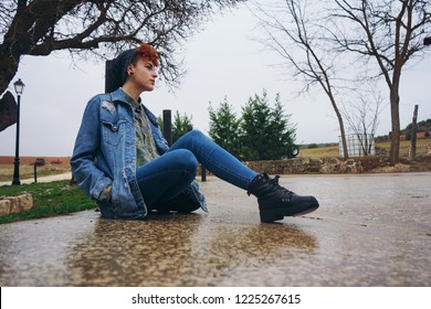 Young redhead woman alone in a village in a rainy day
