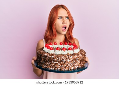 Young redhead woman celebrating birthday with cake angry and mad screaming frustrated and furious, shouting with anger. rage and aggressive concept.