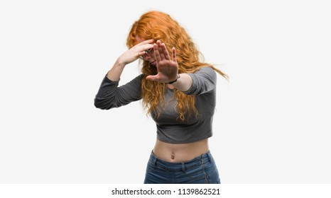 Young redhead woman covering eyes with hands and doing stop gesture with sad and fear expression. Embarrassed and negative concept.