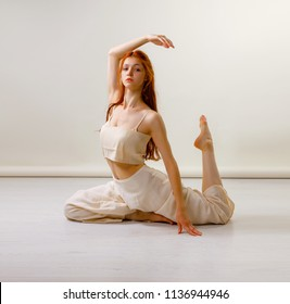 Young redhead woman dancing contemporary dance, posing in studio, sitting on floor. Copy space