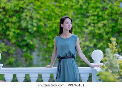 Young redhead woman in dress standing in garden, Greece in spring time