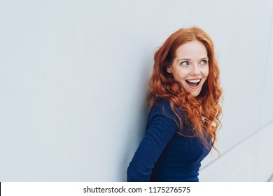 Young redhead woman with an excited expression and mouth open leaning against a white exterior wall with copy space looking off to the side of the frame