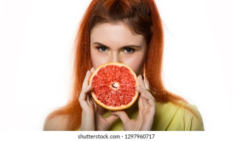 Young redhead woman with a grapefruit on a white background. concept of healthy eating